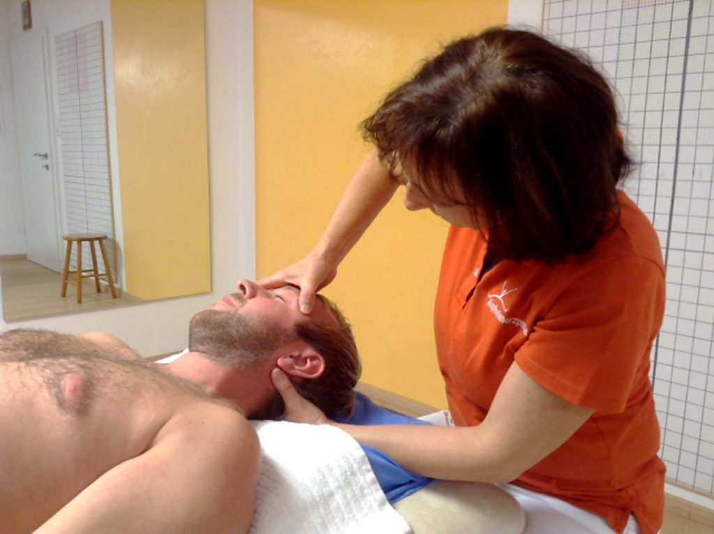 Physiotherapeutin Antonia Reschenhofer behandelt einen Patienten mittels einer Kopf- und Nackenmassage.