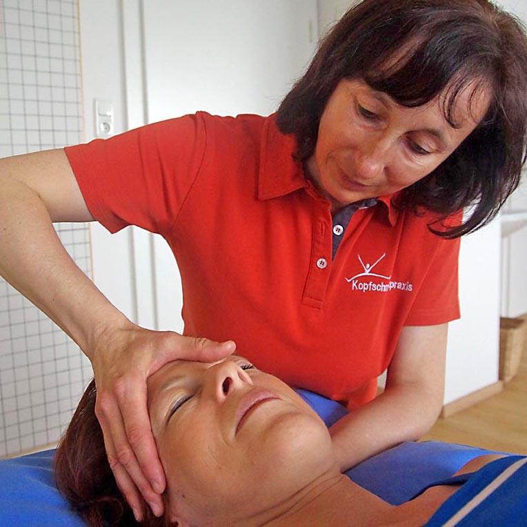 Dipl. Physiotherapeutin Antonia Reschenhofer erklärt Patientin die Fehlstellung anhand eines Wirbelsäulemodells.