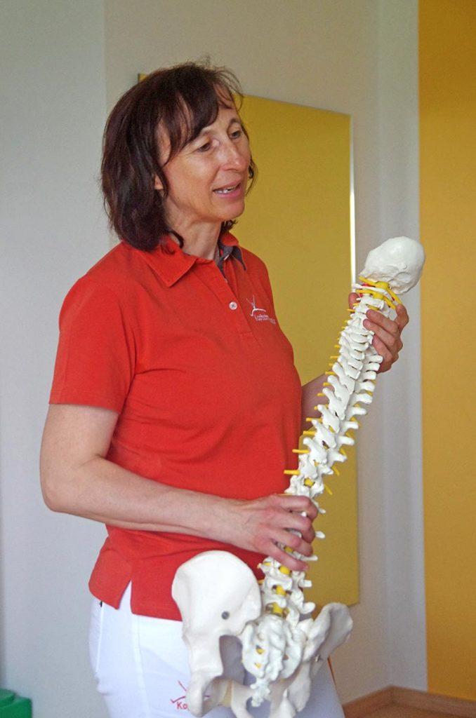 Dipl. Physiotherapeutin Antonia Reschenhofer erklärt mit Hilfe eines Wirbelsäulemodells die Fehlstellung des Patienten.